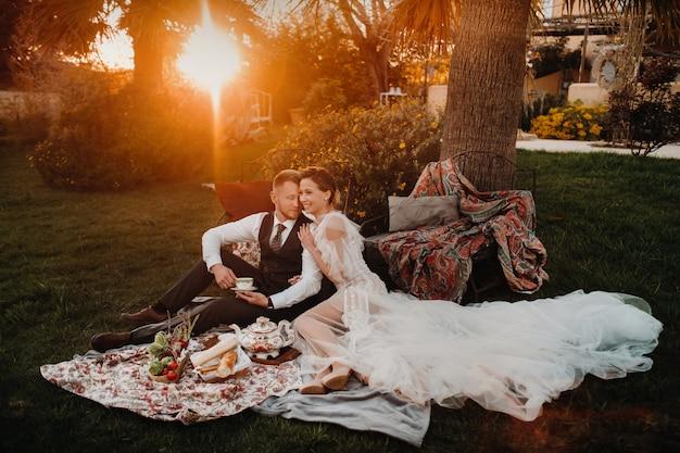 Abendessen des brautpaares beim picknick. ein paar entspannt sich bei sonnenuntergang in frankreich. braut und bräutigam bei einem picknick in der provence.