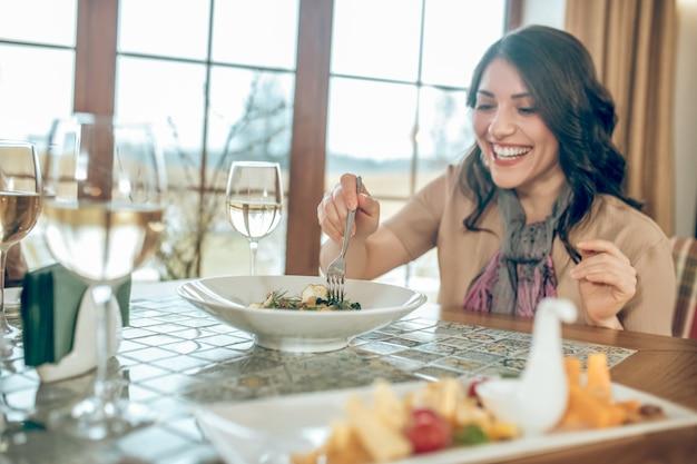 Abendessen. dunkelhaarige süße frau, die in einem restaurant am tisch sitzt und glücklich aussieht looking