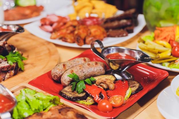 Abendessen-food-konzept. abendtisch mit gegrillter wurst, tortillaverpackungen, biergetränk und verschiedenen tellern auf holztisch, rustikale art.