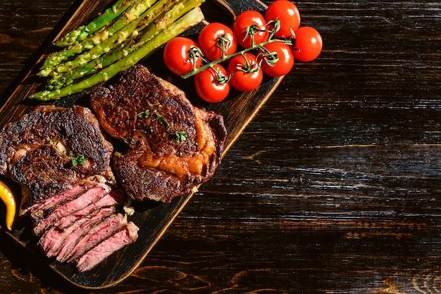 Abendessen für zwei saftige leckere steaks, spargel mit parmesan und gemüse.