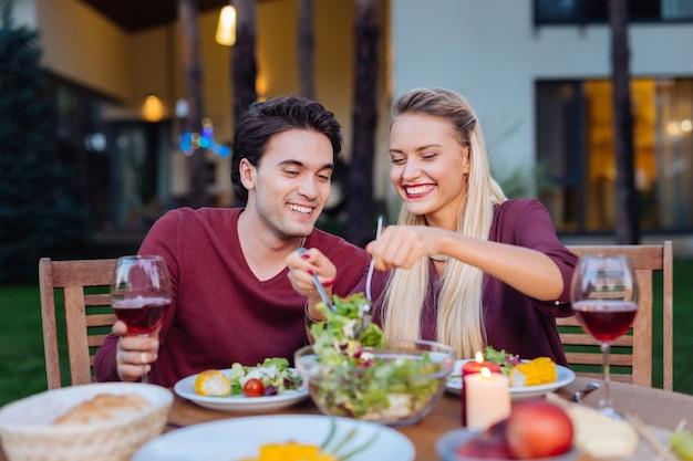 Abendessen im restaurant. erfreutes glückliches paar, das zusammen im restaurant sitzt und sich gegenseitig salat serviert