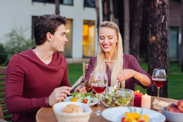Abendessen im restaurant. glückliches entzücktes paar, das zusammen im restaurant sitzt, während sie ihr essen genießen