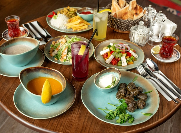 Abendessen mit dolma-suppen, salaten und hühnchen mit reis und pommes frites