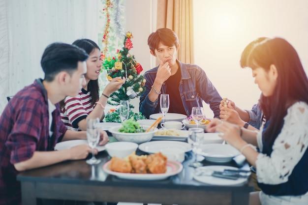 Abendessen mit einer asiatischen gruppe bester freunde, die abends getränke genießen, während sie zusammen am esstisch in der küche sitzen