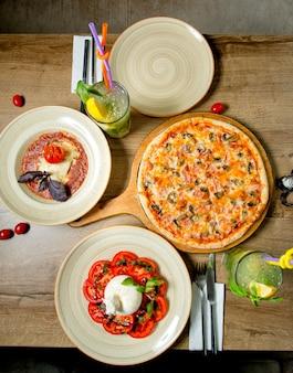 Abendessen mit pizza, salat, limonade und tomatensuppe