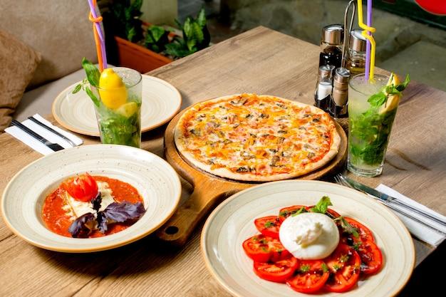 Abendessen mit pizza, salat und tomatensuppe