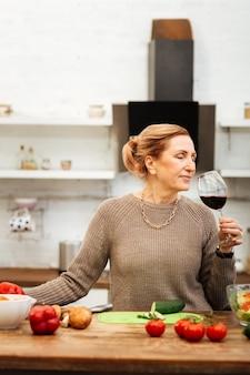 Abendessen vorbereiten. friedliche gutaussehende frau mit gebundenem haar, die einen ruhigen abend hat und rotwein nippt
