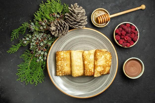 Abendessenhintergrund mit köstlichem pfannkuchenhonig und schokoladenhimbeer- und nadelbaumkegel auf schwarzem hintergrund