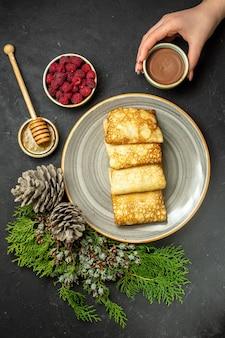 Abendessenhintergrund mit köstlichem pfannkuchenhonig und schokoladenhimbeer- und nadelbaumkegel auf schwarzem tisch