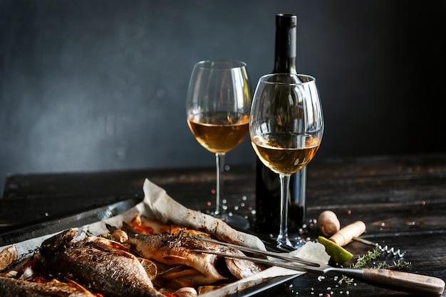 Abendessenkonzept mit zwei gläsern weißwein, gebackener fisch