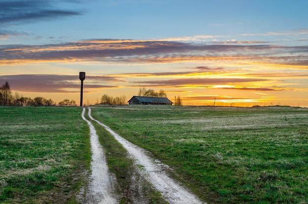 Abendhimmel bei sonnenuntergangsstraße auf dem feld, das zur schuppenscheune und zum wasserturm der ländlichen landschaft des dorfes führt.
