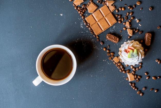 Abendkaffee mit süßigkeiten und keksen auf dunklem tisch