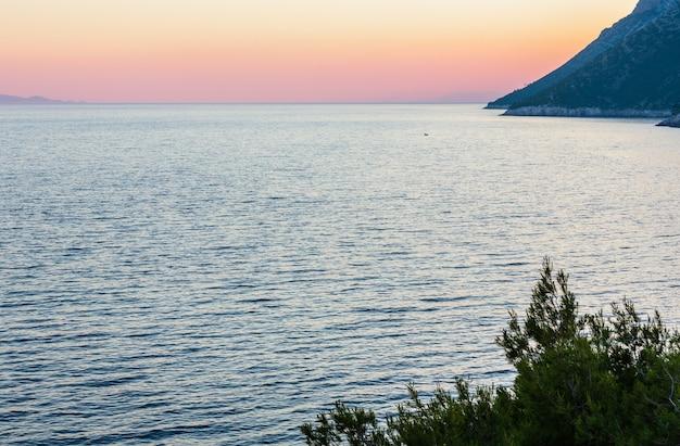 Abendlicher sommerblick auf die küste mit rosa sonnenuntergang und glänzender wasseroberfläche (ston, halbinsel peljesac, kroatien)