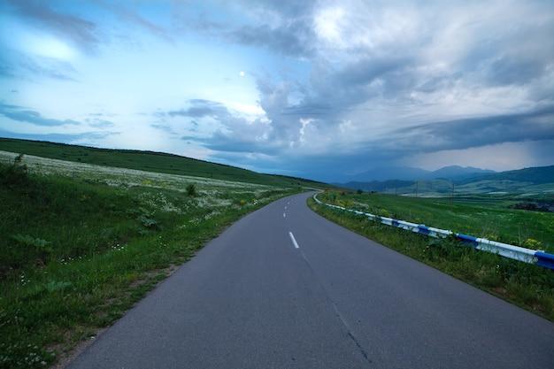 Abends geht eine asphaltstraße durch die felder