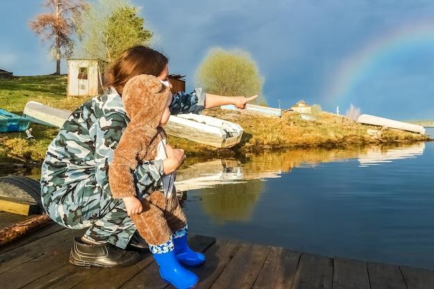 Abends nach einem regen im dorf. eine junge frau zeigt einem kind einen regenbogen am himmel.