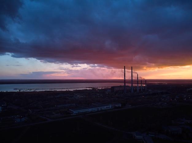 Abends rauchende schornsteine eines wärmekraftwerks vor dem hintergrund eines dramatischen himmels