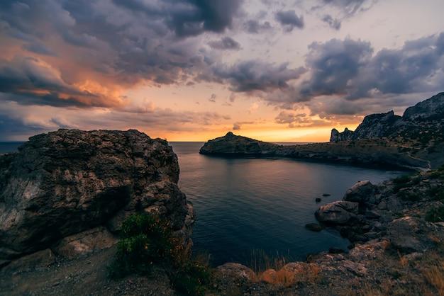 Abendsonnenuntergang in den bergen und im meer mit wolken