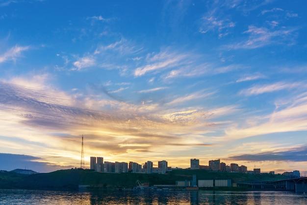 Abendstadt krasnojarsk am ufer des jenissei bei sonnenuntergang. wunderschöne aussicht. gebäude der neuen nachbarschaft. schöner himmel.