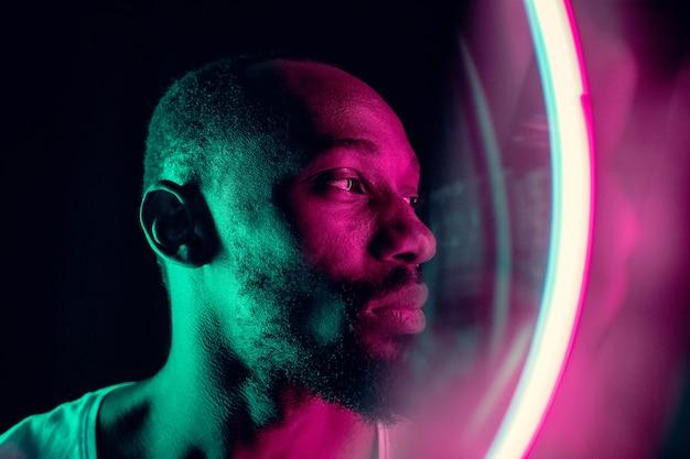 Abendstimmung. filmisches porträt eines stilvollen jungen mannes im neonbeleuchteten raum. helle neonfarben. afroamerikanisches modell, musiker drinnen. jugendkultur im party-, festival- und musikkonzept.
