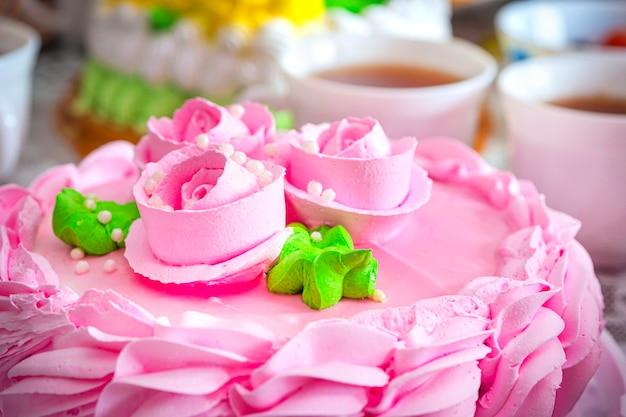Abendtee mit süßigkeiten. rosen und sahne auf dem kuchen. schöne rosa sahnetorte auf dem hintergrund von teebechern.