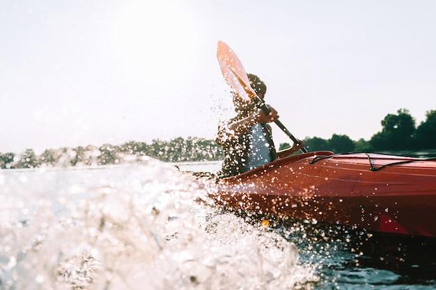 Abenteuer am fluss. junger mann spritzt wasser beim kajakfahren auf dem fluss