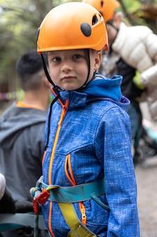 Abenteuer kletterhochseilpark - kleiner junge auf kurs in berghelm und sicherheitsausrüstung