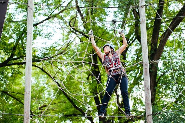 Abenteuer klettern hochseilgarten - frau auf kurs in berghelm und sicherheitsausrüstung