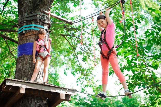 Abenteuer klettern hochseilgarten - wandern in seilpark zwei mädchen