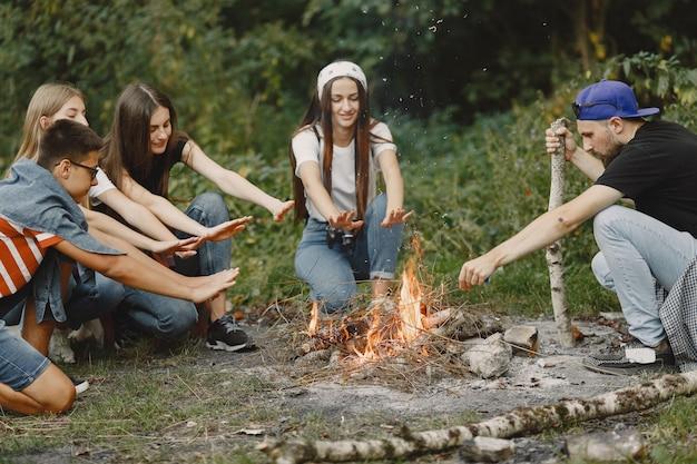 Abenteuer-, reise-, tourismus-, wander- und personenkonzept. gruppe lächelnder freunde in einem wald. leute sitzen in der nähe von lagerfeuer.