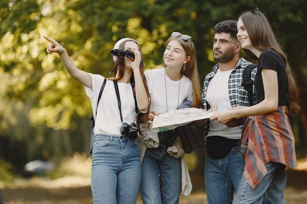 Abenteuer-, reise-, tourismus-, wander- und personenkonzept. gruppe lächelnder freunde in einem wald. mann mit fernglas.
