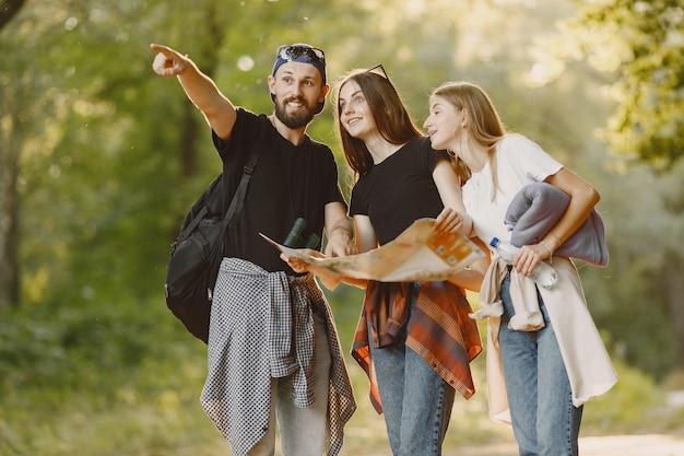 Abenteuer-, reise-, tourismus-, wander- und personenkonzept. gruppe lächelnder freunde in einem wald.