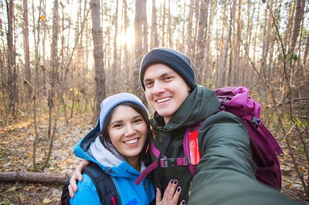 Abenteuer, reisen, tourismus, wanderung und menschenkonzept - touristen lächelndes paar, das selfie über bäumen nimmt.
