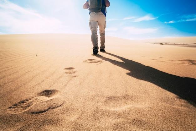 Abenteuer und erkundung auf einem veränderten planeten erde für das konzept der klimaerwärmung - mann von hinten gesehen, der auf wüstendünen mit blauem himmel im hintergrund geht