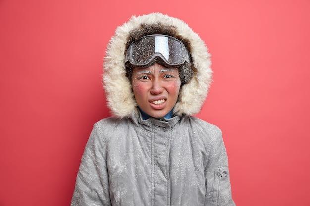 Abenteuerlustige unzufriedene frau zittert vor kälte verbringt viel zeit bei starkem schneesturm geht snowboarden trägt winterjacke.