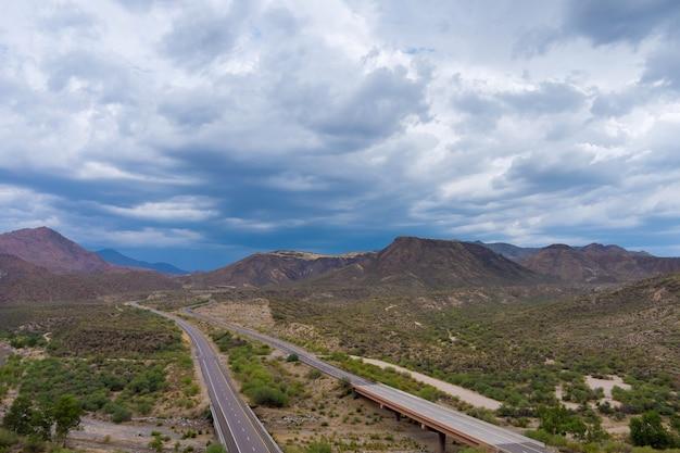 Abenteuerreisende wüstenstraße panoramablick auf die asphaltstraße über die trockenen wüsten von arizona mountains