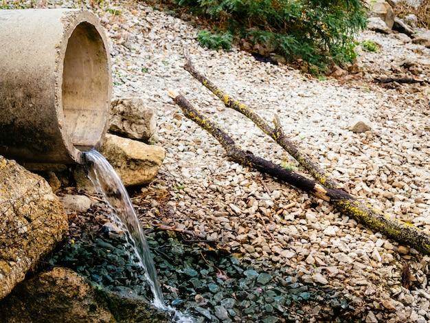 Abfälle aus dem abwasserrohr fließen in den fluss