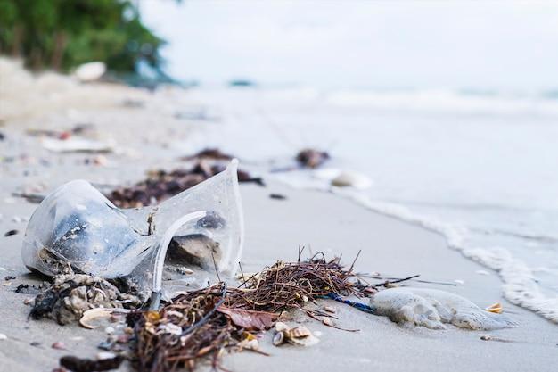 Abfall auf dem sandstrand, der umweltverschmutzungsproblem zeigt