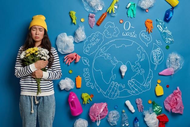 Abfall des umweltkonzepts. traurige düstere asiatische dame hält blumenstrauß fest an sich, besorgt über die globale erwärmung und verschmutzung der erde, denkt über die reinigung des planeten nach.