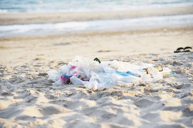 Abfall im meer mit taschenplastikflasche und sandigem schmutzigem meer des anderen abfallstrandes