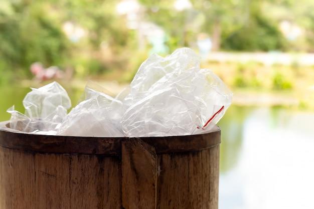Abfallplastiktaschen im hölzernen behälter für die wiederverwertung.