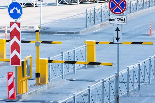 Abflug check-in mit einer barriere für fahrzeuge mit eingezäuntem bereich.