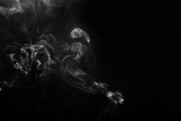 Abgebildeter rauch auf dunklem hintergrund. abstrakter hintergrund, gestaltungselement, für die überlagerung von bildern.