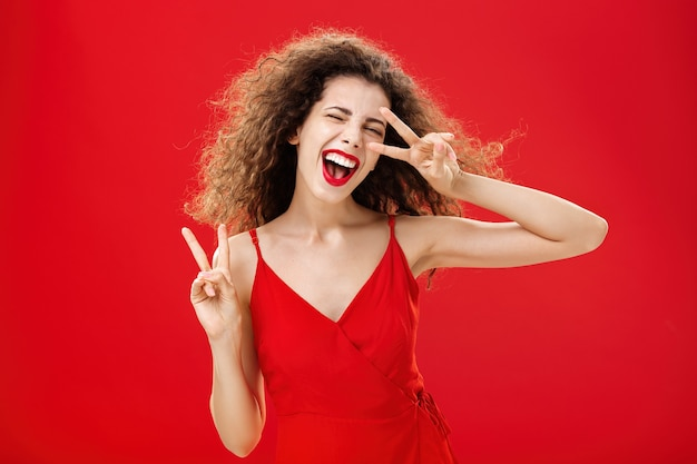 Abgehende freundliche und sorglose junge rebellische frau mit lockiger frisur in rotem stylischem kleid...