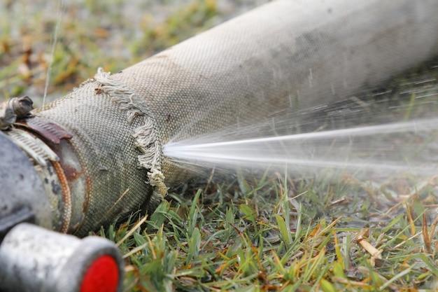 Abgelaufener feuerwehrschlauch, wasser tritt aus.