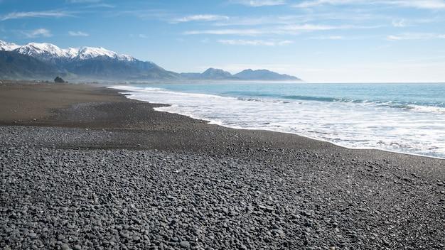 Abgelegener strand mit azurblauem wasser, blauem himmel und bergen im hintergrund kaikouranew zealand