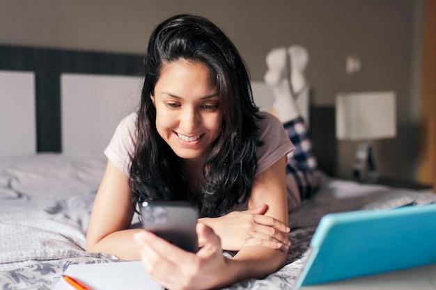 Abgelenktes mädchen, das mitten in einer online-klasse ihr telefon überprüft