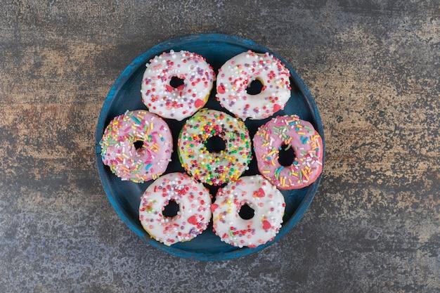 Abgenutzte platte mit mit süßigkeiten bestreuten donuts auf holzoberfläche