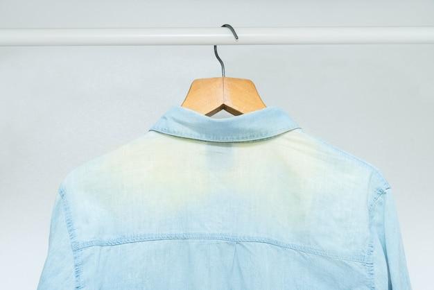 Abgenutztes, ausgebleichtes altes klassisches businesshemd, das in einem kleiderschrank hängt