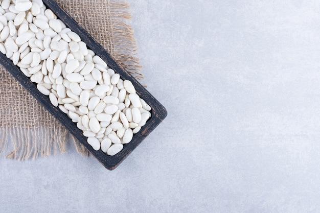 Abgenutztes schwarzes tablett mit marineblauen bohnen auf einem stück stoff, auf marmoroberfläche