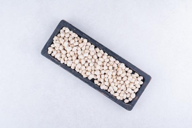 Abgenutztes tablett gefüllt mit einer portion roher kichererbsen auf marmoroberfläche